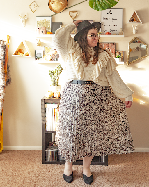 An outfit consisting of a black wide brim fedora, a white oversized sweater with ruffles on a v formation on the front, half tucked unto a cream and dark brown and black leopard print pleated midi skirt and black pointed toe slingback flats.