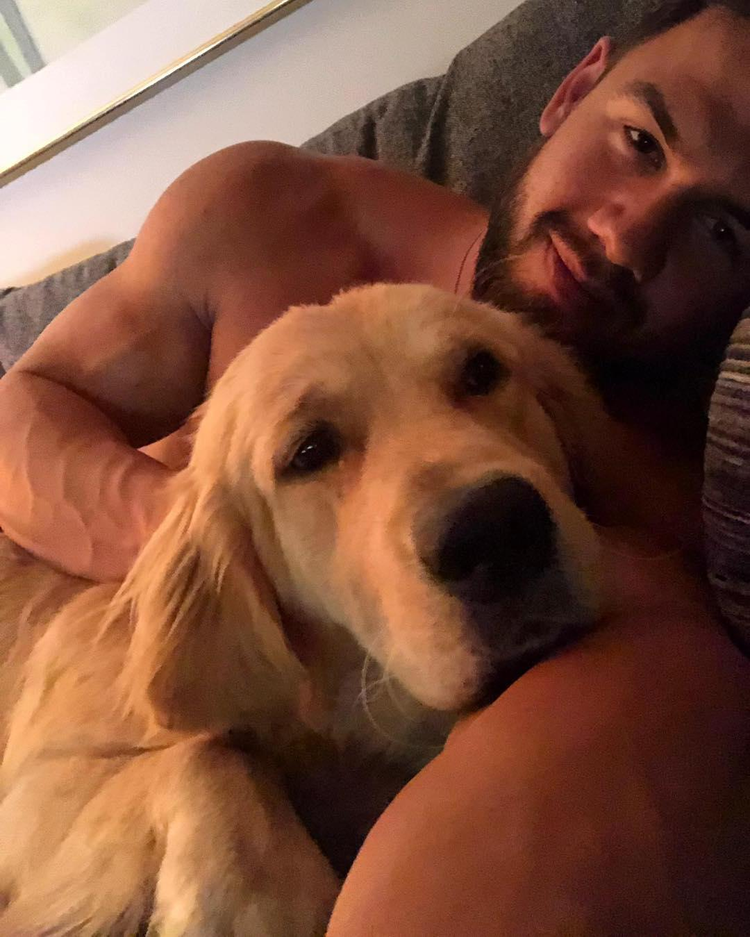 handsome-bearded-nude-dude-laying-selfie-with-adorable-yellow-labrador-puppy-dog