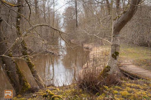 Taciņa upes krastā un laipa pāri kanālam