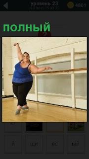 В зале полный человек совершает упражнения для похудения держась за поручни