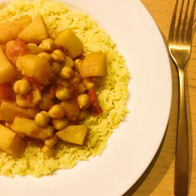 slow cooker potato and chickpea curry on top of turmeric rice. Gold cutlery next to plate
