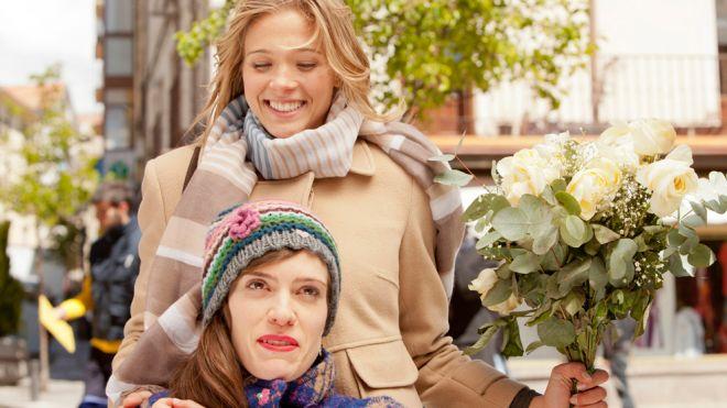 fotograma muy colorista donde Alba, que sujeta un gran ramo de flores, está junto a su amiga Andrea, las dos sonrientes