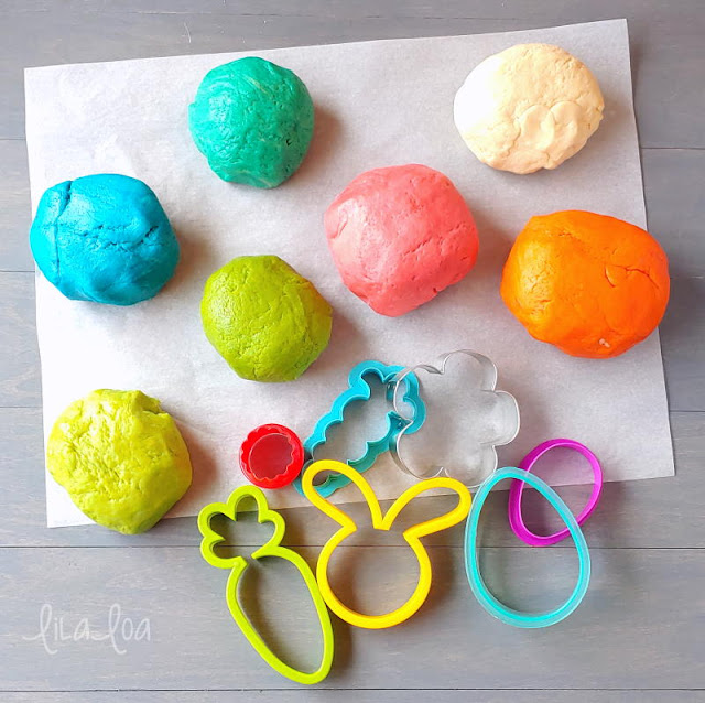 Colorful balls of cookie dough and Easter cookie cutters