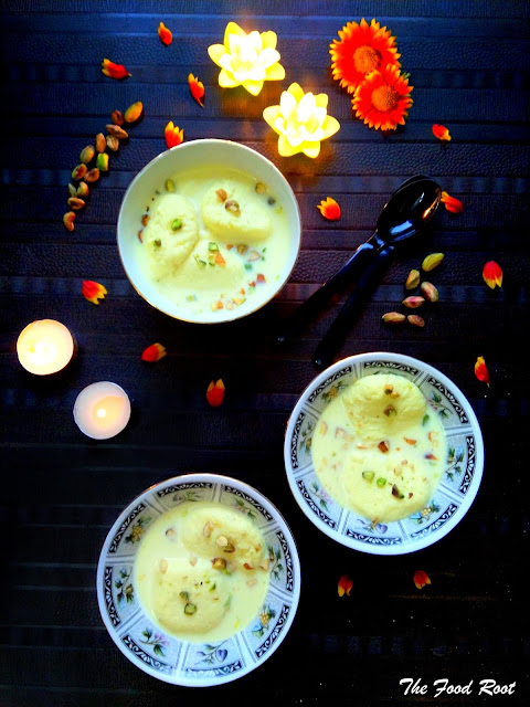 Easy Homemade Rasmalai Recipe for Diwali topped with nuts and decorated with diyas and flowers.