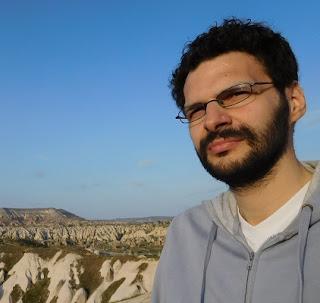 Foto de Javier Conejo en el monte, en el que un hombre joven con gafas, pelo coto, rizado y oscuro, así como la barba, viste una sudadera azul claro.