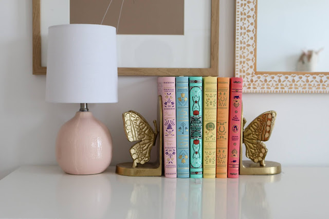 Dresser styling with a rainbow book set, brass bookends, and a mini table lamp
