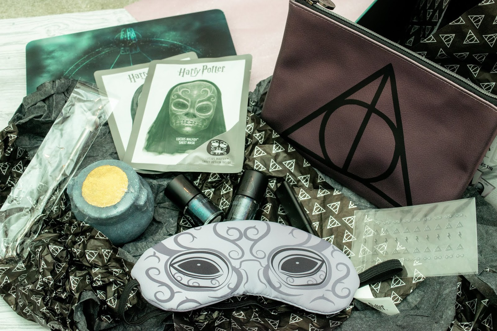 A flat lay of beauty products in black and grey. There are face masks, a pouch, bath bomb, nail polish, eye mask and makeup brush.