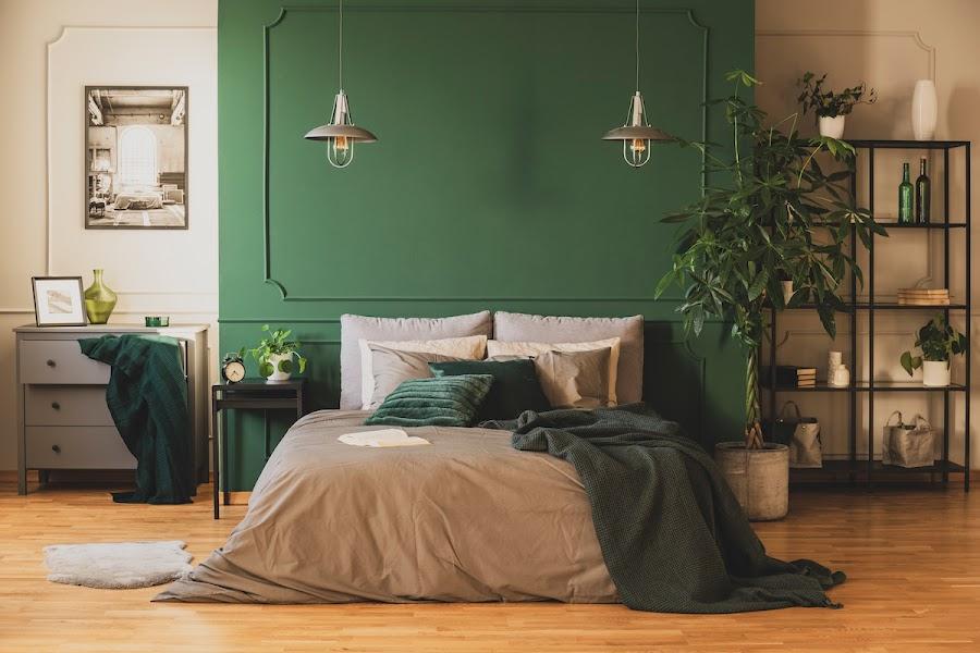 Dormitorio con frente pintado de verde y cómoda gris, con lámparas colgantes