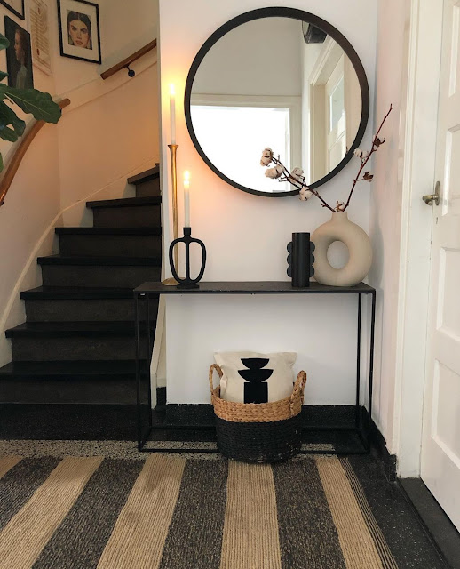 bohemian entryway with striped jute rug, round mirror above console table, and modern donut vase