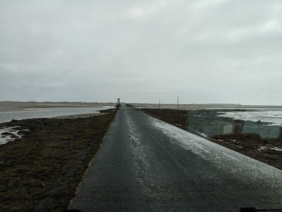 Photo of the causeway to Holy Island with the tide well out but traces of water and sand on the road.