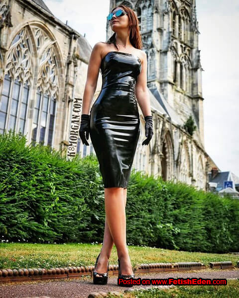 Red-heaired lady in black latex midi-dress wears sunglasses and black high heels outdoors