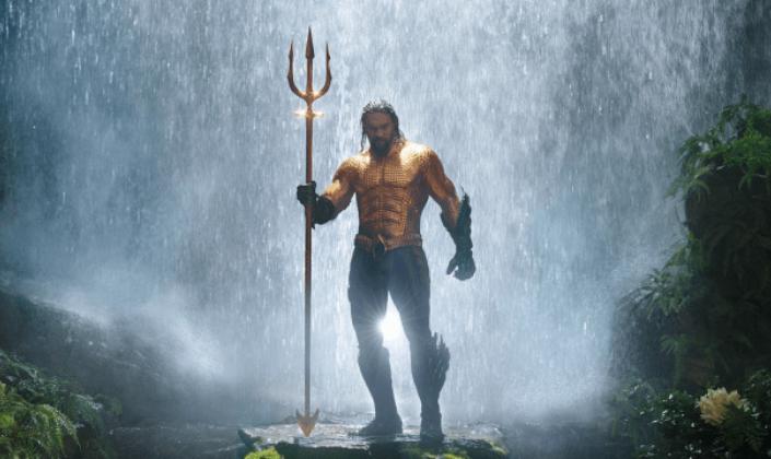 Imagem de capa: o personagem Aquaman, interpretado por Jason Momoa, um homem de cabelos loiros com uma barba, vestido em uma armadura de escamas douradas, luvas e botas verde-escuras e segurando um tridente dourado, por trás uma cachoeira estrondosa caindo.