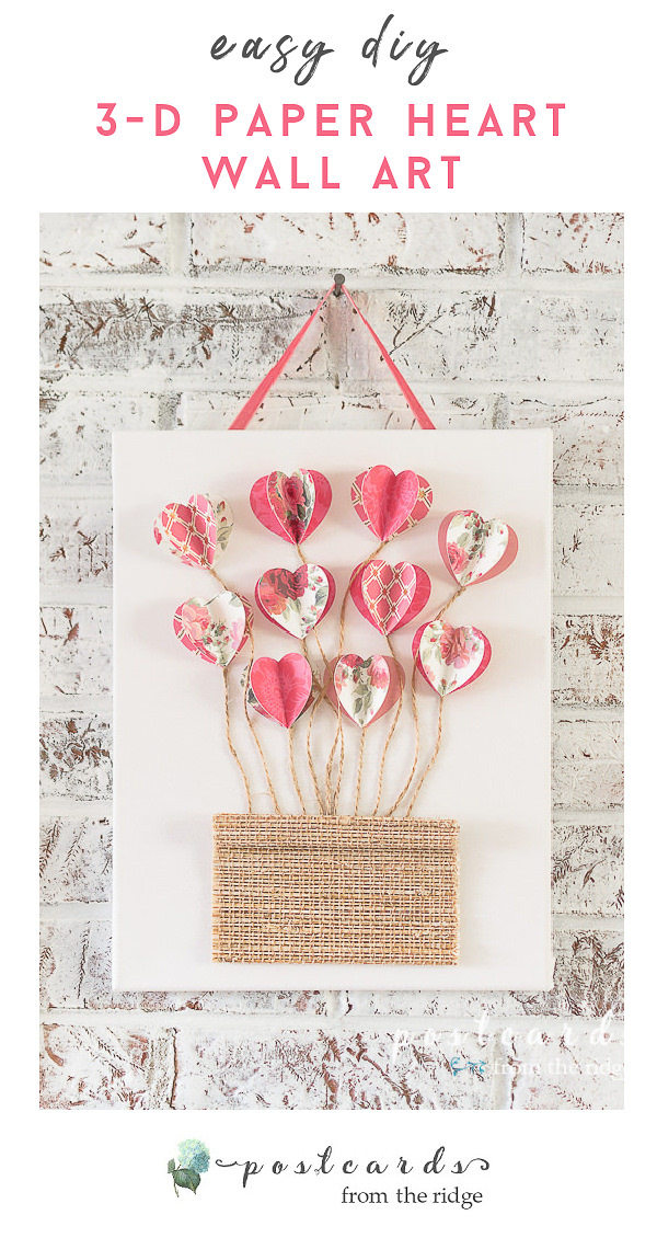 3-D paper hearts with twine on white canvas