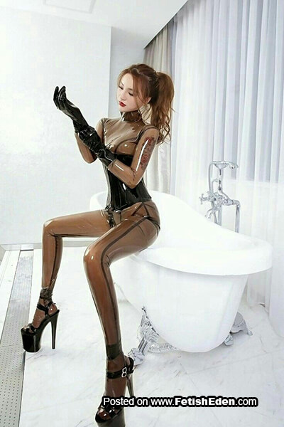 Translucent latex catsuit Asian babe in black high heels puts on short black latex gloves