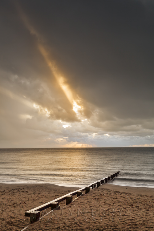 Rays of sun pierce the storm clouds over Swanage beach in Dorset