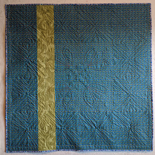 A blue stripe fabric with a single insert strip of light green creates a back for the quilt