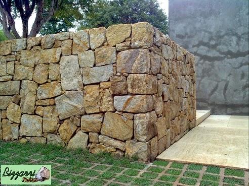 Detalhe do muro de pedra madeira amarela com o piso de pedra de mármore travertino.