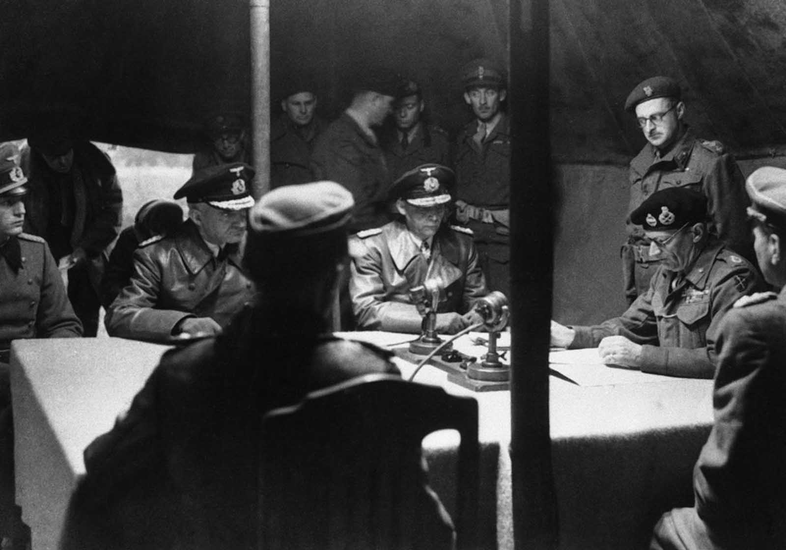 Britain's Field Marshal Bernard Montgomery, right, reads over the surrender pact, while senior German officers, from left, Major Friedel, Rear Admiral Wagner and Admiral Hans-Georg Von Friedeburg, look on, in a tent at Montgomery's 21st Army Group headquarters, at Luneburg Heath, on May 4, 1945. The pact agreed a ceasefire on the British fronts in north west Germany, Denmark and Holland as from 8am on May 5. German forces in Italy had surrendered earlier, on April 29, and the remainder of the the Army in Western Europe surrendered on May 7 -- on the Eastern Front, the German surrender to the Soviets took place on May 8, 1945. More than five years of horrific warfare on European soil was officially over.