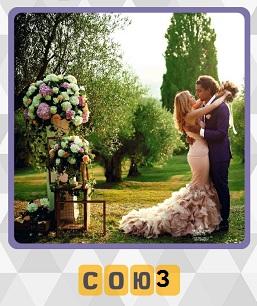 на поляне стоят и обнимаются мужчина и женщина с букетом цветов, заключая брачный союз