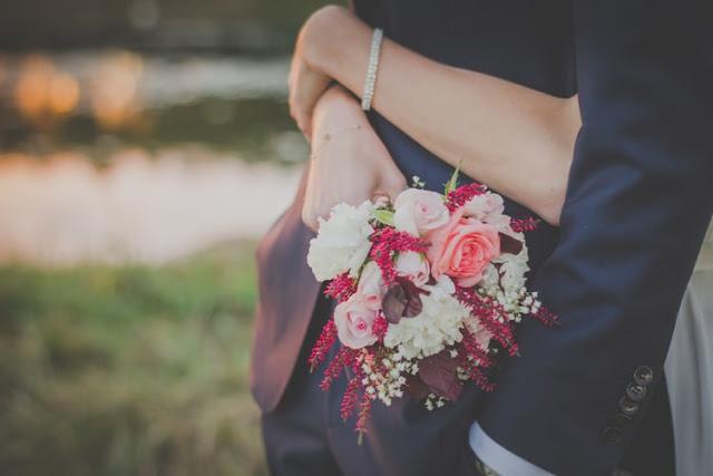 zakochana para kobieta od tyłu obejmuje mężczyznę trzymając w ręce bukiet kwiatów
