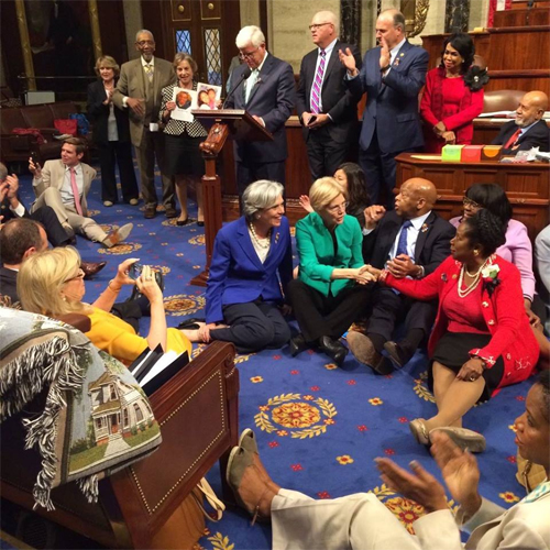 image of the Democratic sit-in yesterday, showing a number of House members sitting on the floor together, congregated around John Lewis; Senator Elizabeth Warren has joined them in solidarity