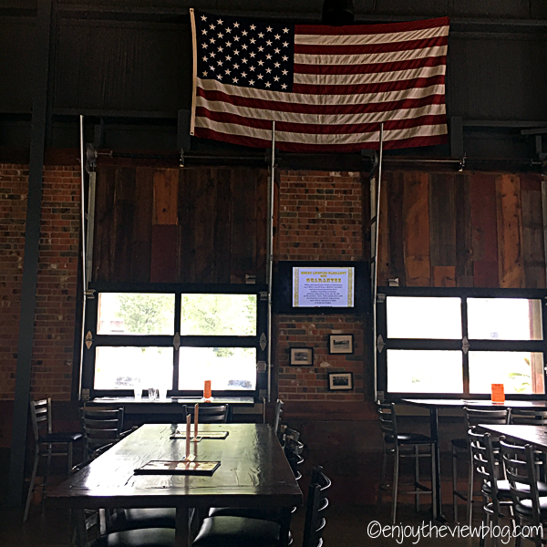 wooden tables and chairs inside a room with red brick walls and a USA flag hanging on the wall