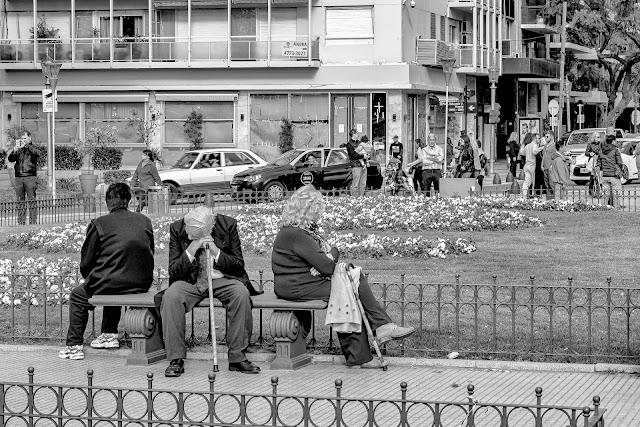 B&W. Adulto mayor sentado en banco de plaza recostado sobre su bastón.