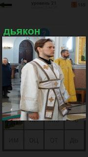 В помещении церкви идет служба и дьякон стоит около алтаря