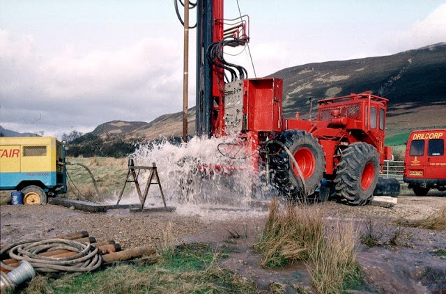 Bridge Farm borehole, Machrie, Arran. Drilling a groundwater production borehole for West of Scotland Water at Machrie, Arran.  The drill rig is located close to the 'String' road from Brodick at a site chosen by the Hydrogeology Group of BGS. The rig is using an air flush hammer to drill through Permian sandstone. The compressor is seen at the left. Compressed air is sent down the drill rods to the hammer at the bottom of the borehole. The air operates the hammer and brings cuttings and water to the surface. The water flows away from the site to a stream. The 4-wheel drive tractor unit powers the rig and is highly manoeuvrable - useful for sites with problematical access.