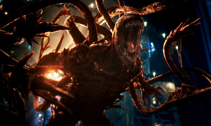 Imagem de capa: o personagem Carnificina, uma criatura humanóide parecida com Venom, com o corpo composto por uma matéria avermelhada, os olhos grandes indo até em cima da cabeça, sem pupilas, a boca enorme aberta com dentes afiados e uma longa língua, garras afiadas e vários tentáculos que surgem a partir de suas costas que terminam em espigões afiados.