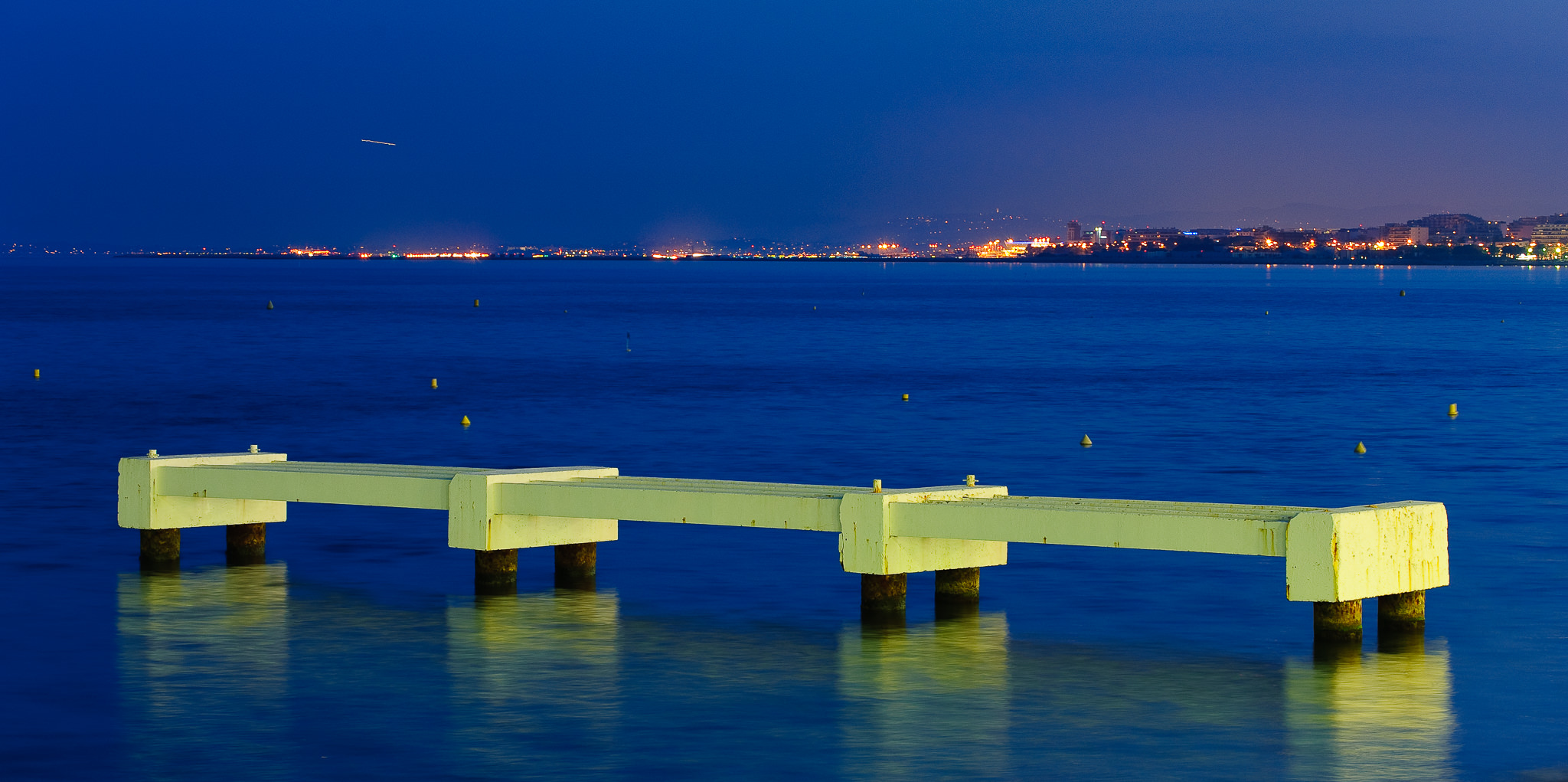 a fine art photo of a floodlit pier at night in nice france