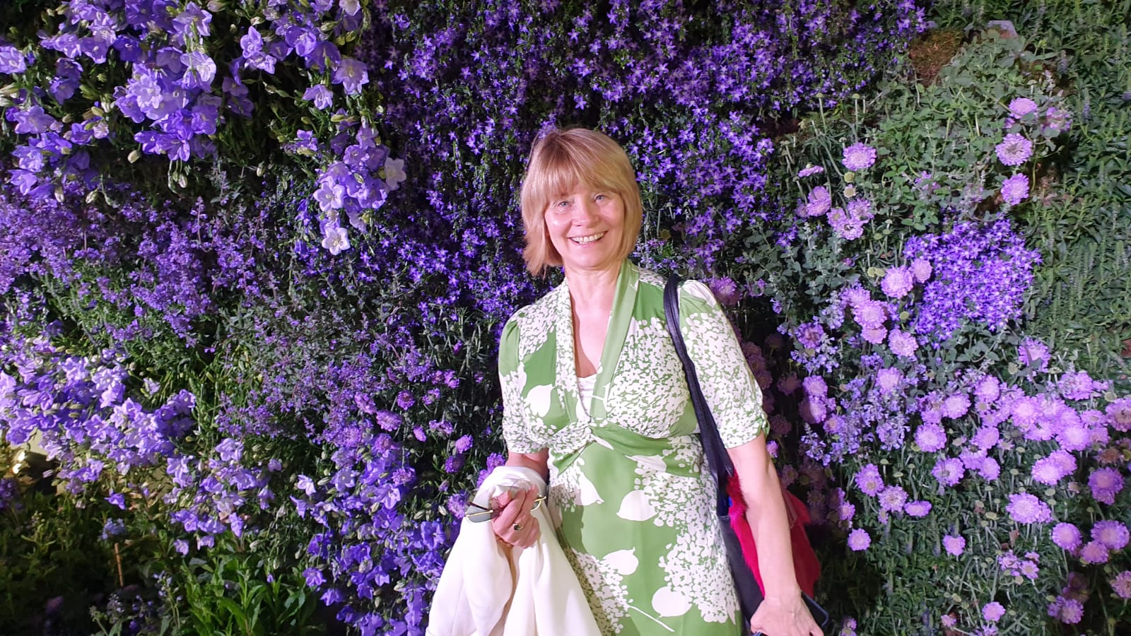 Wearing a green hydrangeas print dress with a backdrop of purple flowers at the Chelsea Flower Show
