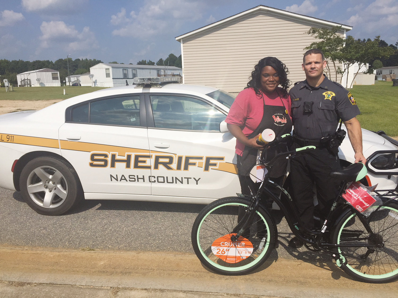 Jaylesya Corbett receives a Schwinn women's bicycle from Nash County sheriff's Sgt. Scott Bass in August.