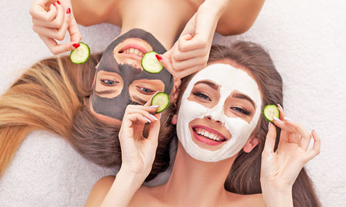 Chicas jovenes con mascarilla facial y pepino