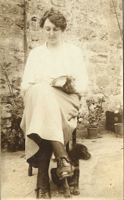 Young girl seated with book and puppy at her feet