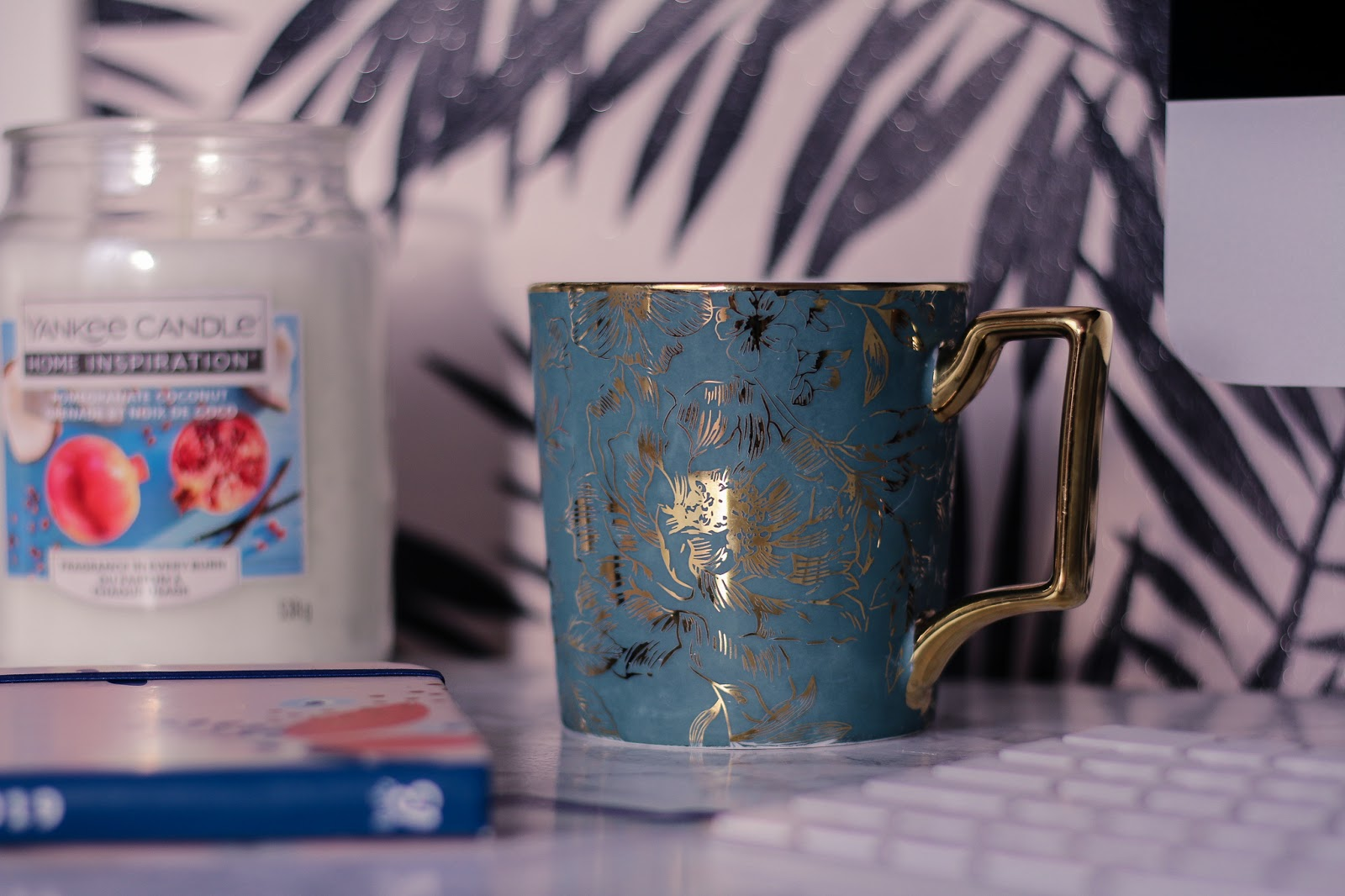 Close up photo of a blue mug on a white marble desk top with a white yankee candle next to it and a 2019 busy b diary