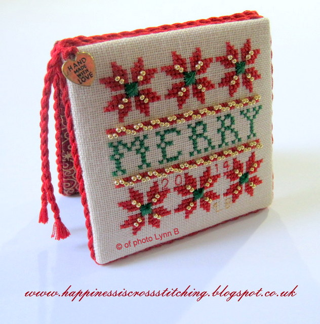 Christmas Cross stitch finished into a flat fold ornament stitched using red and green threads and trimmed with gold coloured beads