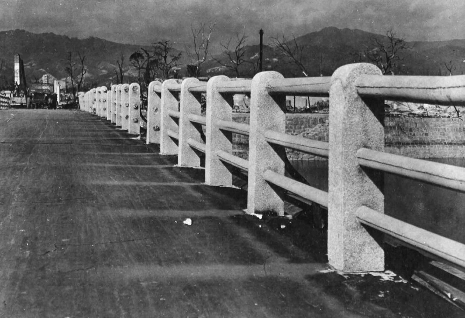 The searing heat from the nuclear explosion above Hiroshima scorched the roadway of this bridge across the Ota River, about a half a mile from the focal point of the bomb burst. The areas shielded by the concrete pillars and railings were left undamaged, creating permanent