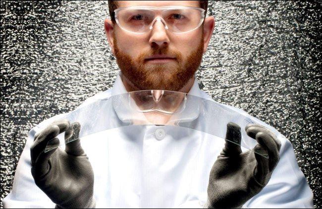 عالم يحمل قطعة من زجاج كورنينج القابل للانحناء.