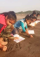 Girls of onjal village use sand surface as a notebook to write the lessons