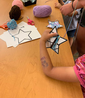 child wrapping yarn around a paper stock star with balls of yarn and star cutouts on the table below