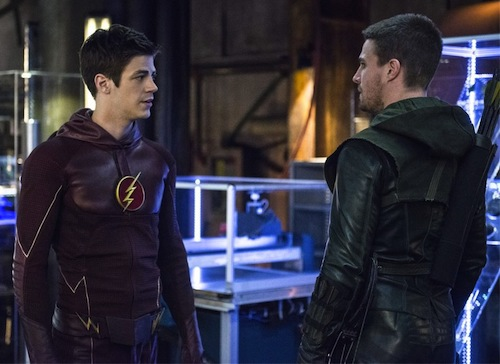 Grant Gustin as The Flash and Stephen Amell as The Arrow facing one another, maskless, in the so-called Arrow Cave