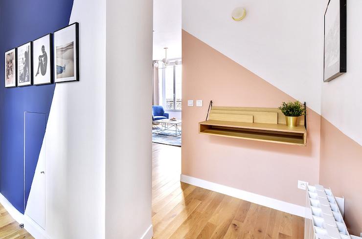 Pasillo abierto al salón con pintura azul y salmón con forma geométrica.