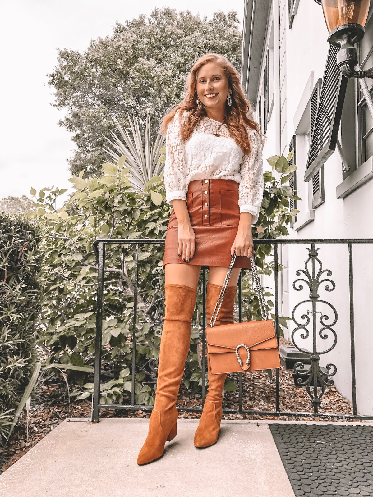 St Pete blogger Amanda Burrows is wearing a faux leather skirt and white lace top. She is also wearing a pair of over the knee boots and is holding a Gucci bag in her hand.