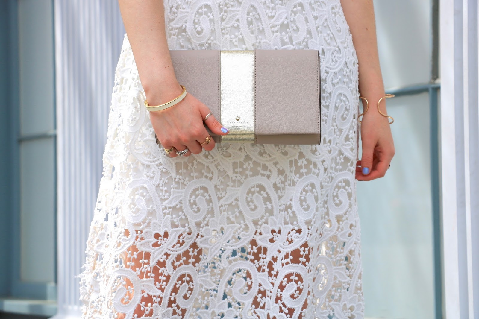 nyc fashion blogger Kathleen Harper holding a gold Kate Spade clutch