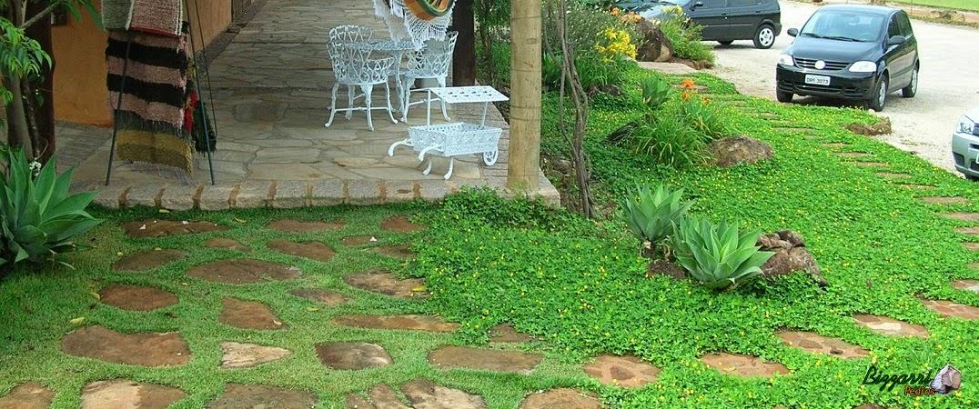 Caminho no jardim com pedra moledo grande tipo chapada com a execução do paisagismo com grama amendoim.