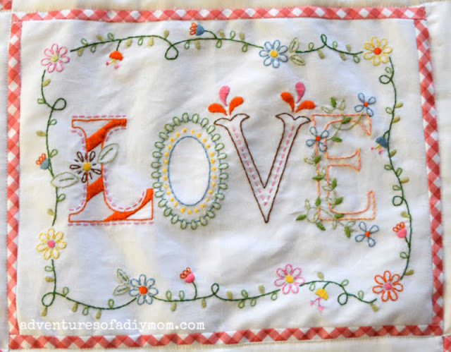 an embroidered piece of fabric with the word love and bordered with flowers