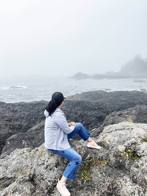 Vancouver beauty, life and style blogger Solo Lisa sits on a rock at Chesterman Beach, Tofino, BC, looking out to the ocean. It is a cloudy day.