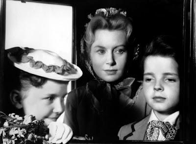 Miss Giddens (Deborah Kerr) accompagnée de Flora (Pamela Franklin) et Miles (Martin Stephens)