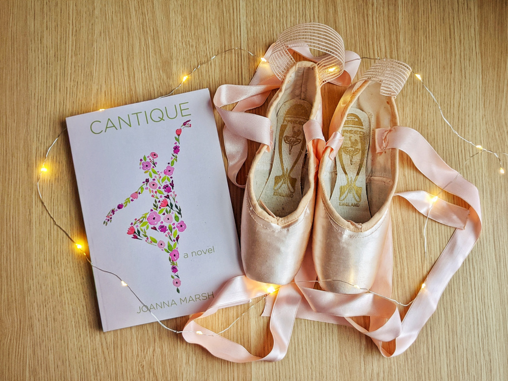 Novel Cantique by Joanna Marsh, fairy lights, and pointe shoes.